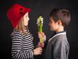 Boy offering flower on black background. Valentines day concept.
