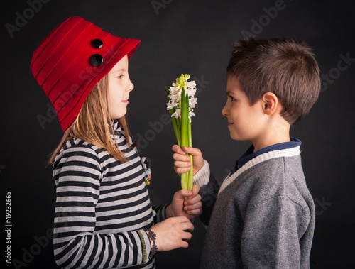 Boy offering flower on black background. Valentines day concept.