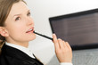 Thinking woman presenting laptop screen and pen