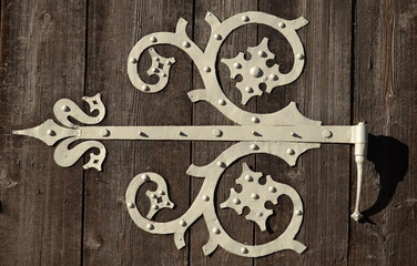 Close-up Of An Ornamental Hinge On An Old Wooden Door