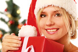 Young woman in santa hat holding a gift box