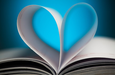 sign of heart with book pages on the blue