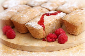 delicious cakes with raspberries on wooden background, close-up