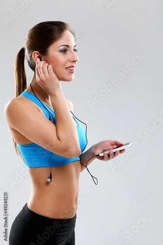 Young woman in fitness wear with headphones