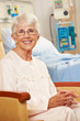 Portrait Of Senior Female Patient In Chair By Hospital Bed