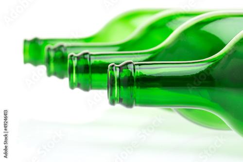 Liegende grüne Flaschen auf weißem Hintergrund