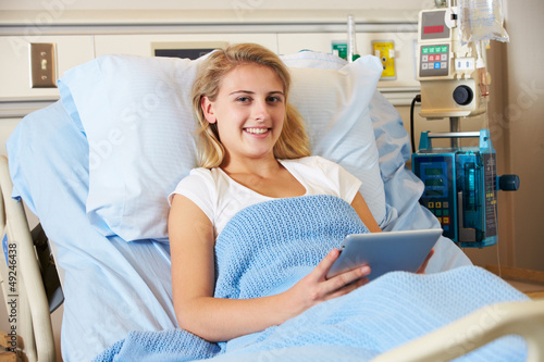 Teenage Female Patient In Hospital Bed With Digital Tablet