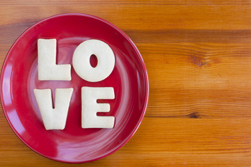 Love letters cookies on a red plate.
