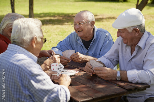 canvas print picture Active seniors, group of old friends playing cards at park