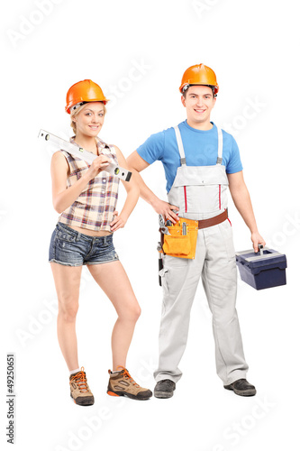 Team of a male and female construction workers holding tools