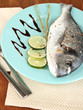 Fish dorado with lemon on plate on wooden table close-up