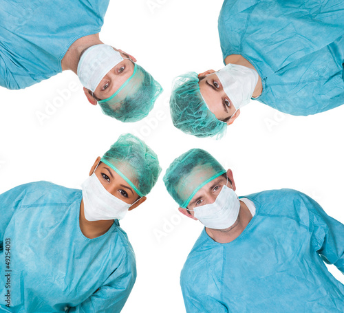 Four surgeon looking down at patient