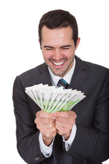 Excited businessman holding euro notes