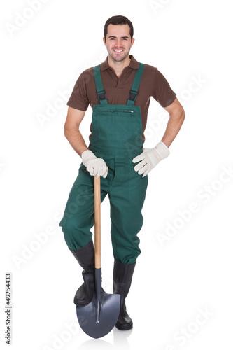 Leinwandbild Motiv Happy young gardener in dungarees