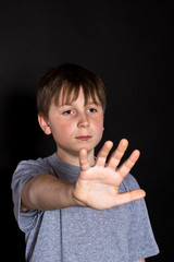 boy shows his hand to stop