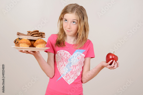 Young girl deciding junk food or apple