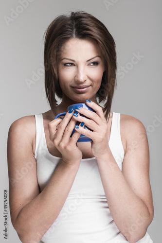 Hübsche Frau hält eine blaue Tasse