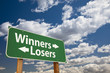 Winners, Losers Green Road Sign Over Clouds