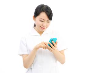 スマートフォンを持つ看護婦