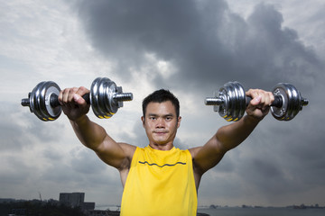 Athletic Young Chinese man exercising outdoors with dumbbells
