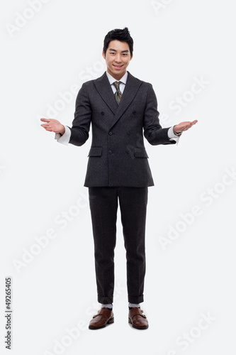 Young Asian business man showing welcom sign.