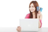 beautiful young woman holding credit card with laptop