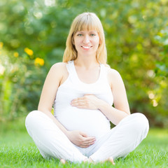 Happy pregnant woman in park