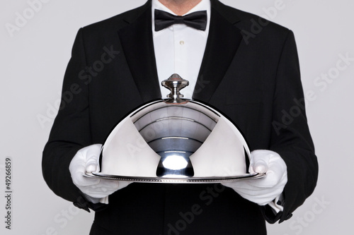 Waiter holding a silver cloche - 49266859