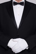 Man in a tuxedo wearing white gloves.