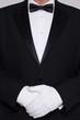 Man in a tuxedo wearing white gloves.