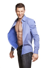 handsome athletic man opens his blue shirt and smiling on white
