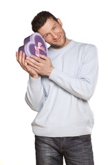 handsome guy in a blue blouse and jeans holding purple gift