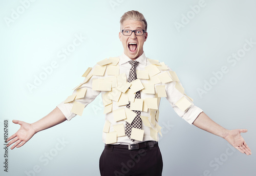 Frustrated businessman covered by blank post-it notes.