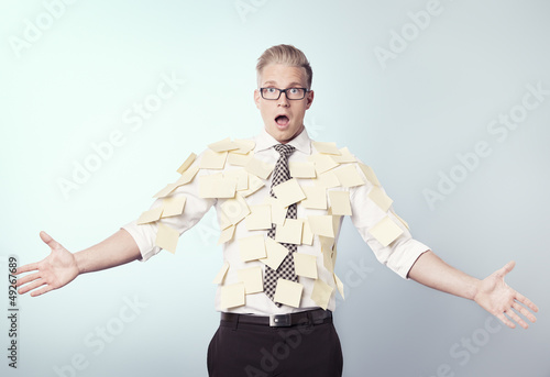 Shocked businessman covered by blank post-it notes.