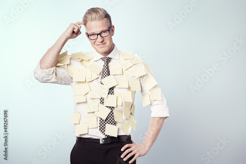 Puzzled businessman with stickers attached to his shirt.
