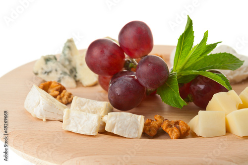 Various types of cheese with nuts and grapes on plate