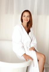 Schöne junge Frau sitzt auf der Badewanne