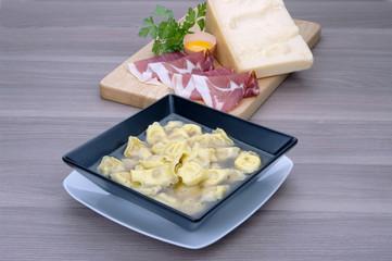 Tortellini in brodo alla bolognese su tavolo in legno