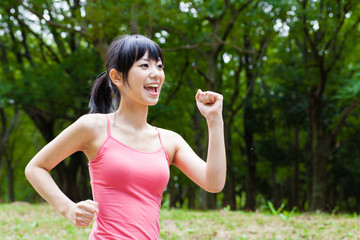 attractive asian woman jogging in the park
