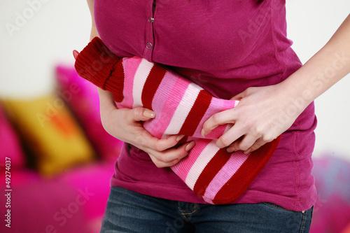 Leinwandbild Motiv Frau hält Wärmflasche bei Bauchschmerzen