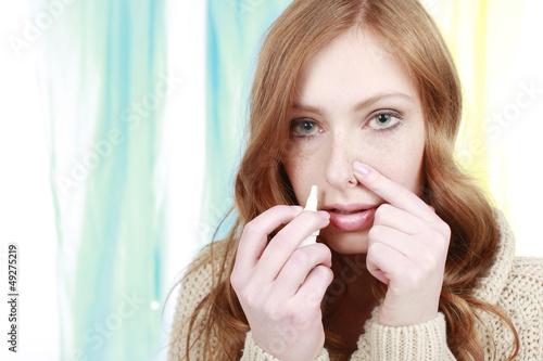 Junge Frau benützt bei Erkältung Meerwasser Nasenspray
