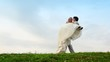 groom takes bride on hands and carries away it on meadow