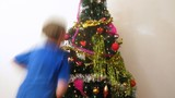 Brother and sister decorate New Year tree by New Year