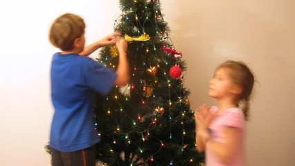 Girl and boy decorate New Year tree by New Year
