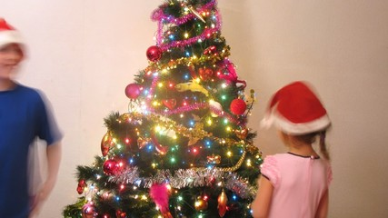 Girl and boy decorate New Year tree by New Year in hats of Santa