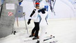 skier instructor helps girl and they go up together on hill in