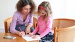 Mother with her daughter sit on chairs at wooden table and draw