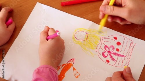 Mother and her daughter draw with colored markers, only hands