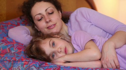 Mother and daughter sleep on bed, then they wakes and mom kiss