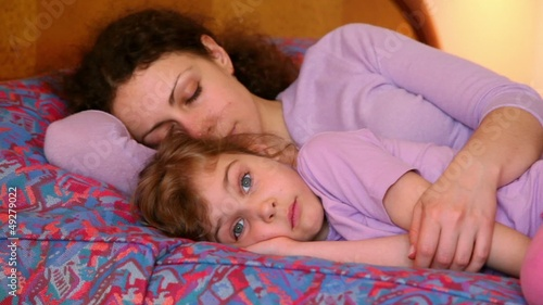 Mother with daughter lay on bed, mom sleeps but girl makes faces